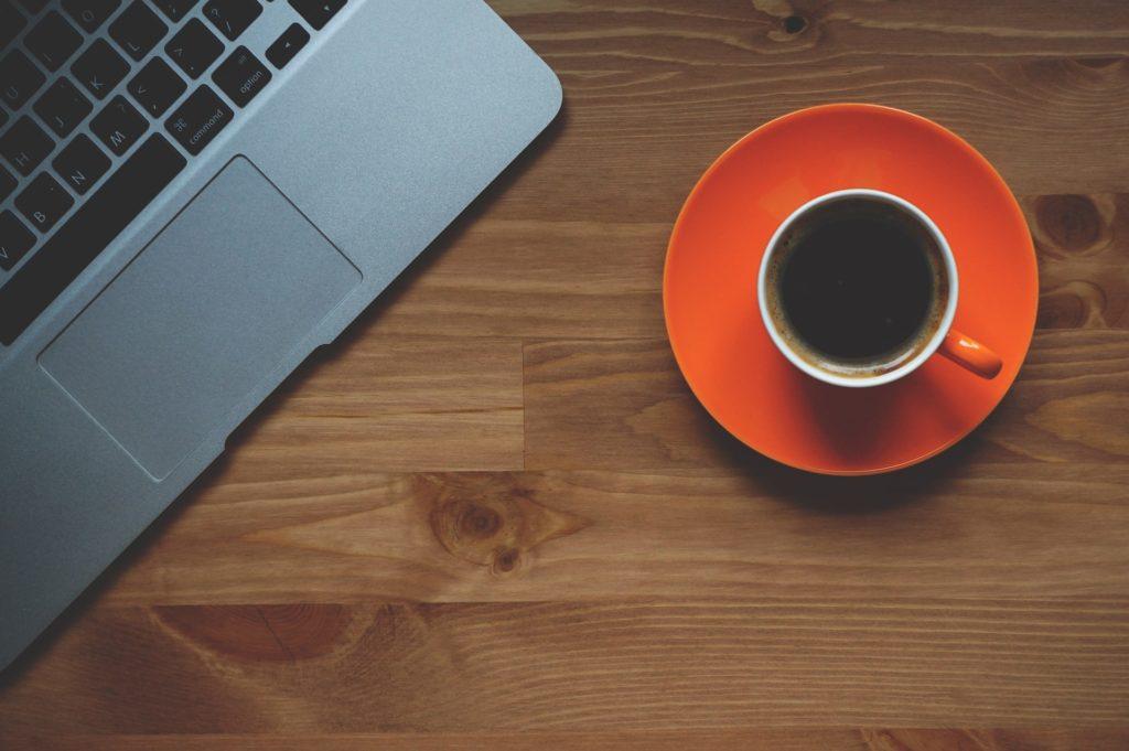 achats avec ordinateur, café et carnet sur un bureau